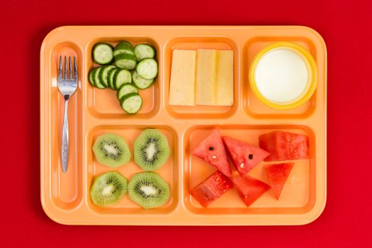 Lunch tray with fork, fruit, cheese and milk