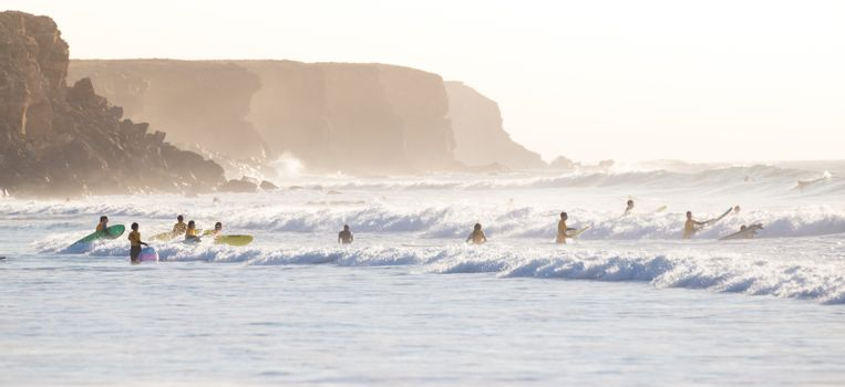 EL Cotillo, Spain - Dec 17, 2015:  Active sporty people having fun learning to surf on El Cotillo beach, famous surfing destination on Fuerteventura, Canary Islands, Spain on December 17, 2015.