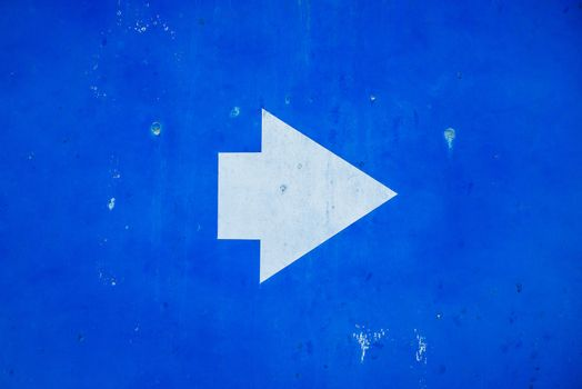 Direction sign white arrow symbol on blue painted grunge metal background.