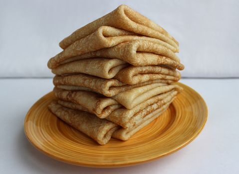 Pancakes with butter on a plate, as a symbol of ancient Slavic celebration of Carnival. Meet spring, winter farewell.