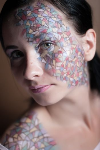 Portrait of a beautiful young girl with creative makeup mask pattern of bright colors.