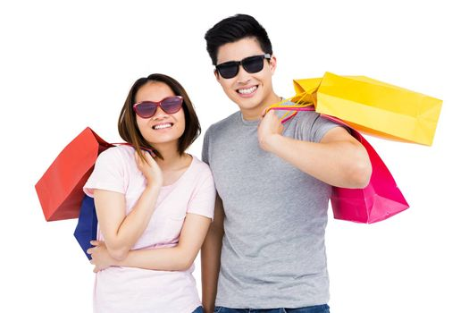 Young couple holding shopping bags and smiling on white background