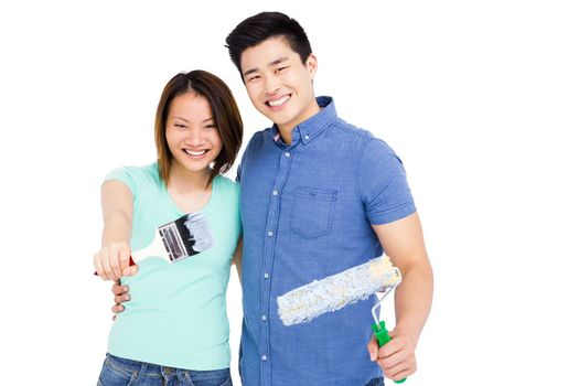 Young couple holding paint brush and paint roller on white background