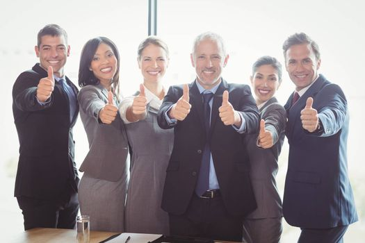 Portrait of businesspeople standing together and giving thumbs up in office