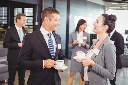 Businesspeople having tea and interacting during break time in office