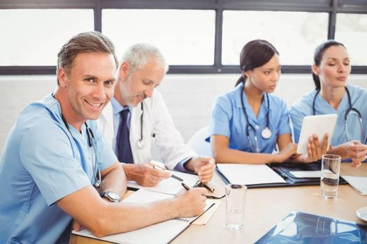 Portrait of male doctor smiling in conference room and colleagues discussing in background