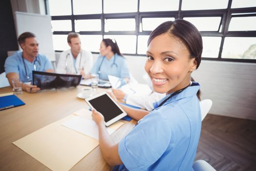 Portrait of female doctor holding digital tablet in conference room and colleagues discussing in background
