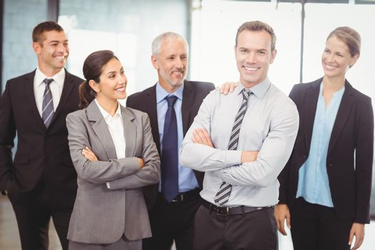 Businesspeople standing with arms crossed in office