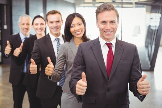 Portrait of businesspeople giving thumbs up in office