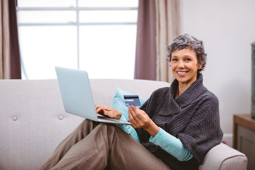 Happy mature woman with credit card using laptop