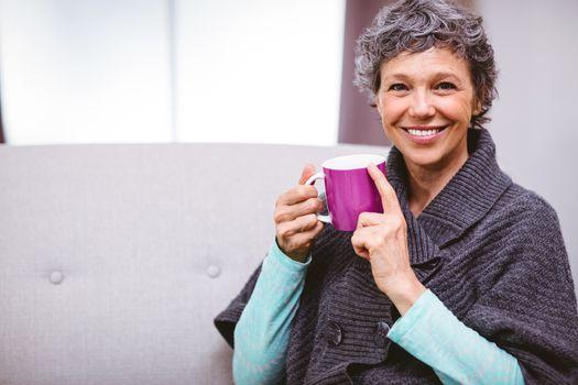 Mature woman with coffee mug sitting on sofa