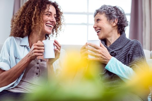Smiling mother and daughter holding coffee mugs while discussing