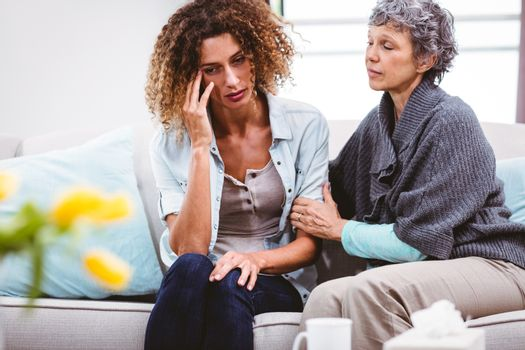 Mother comforting sad daughter sitting on sofa