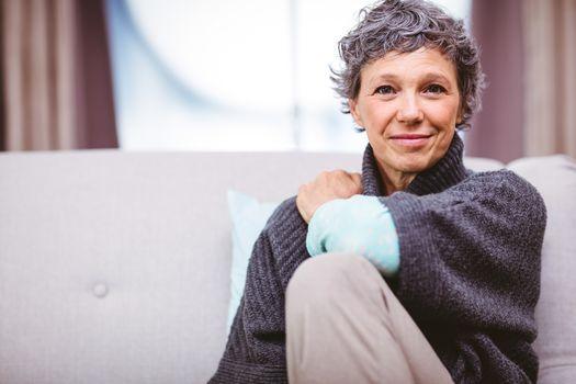 Portrait of smiling mature woman sitting on sofa