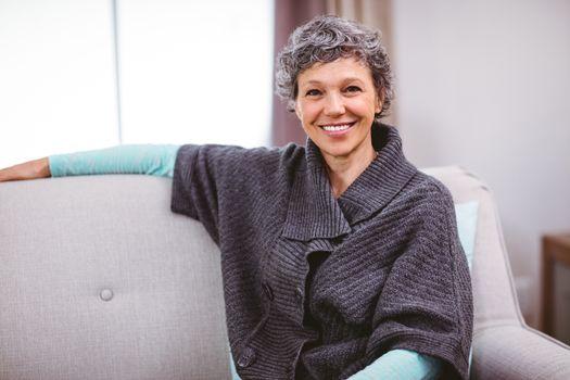 Portrait of cheerful woman sitting on sofa