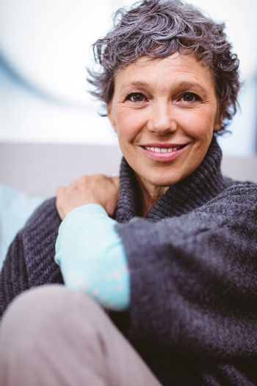 Portrait of happy mature woman sitting on sofa