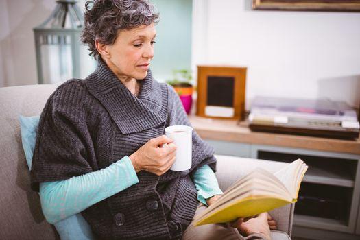 Mature woman reading book and holding coffee mug