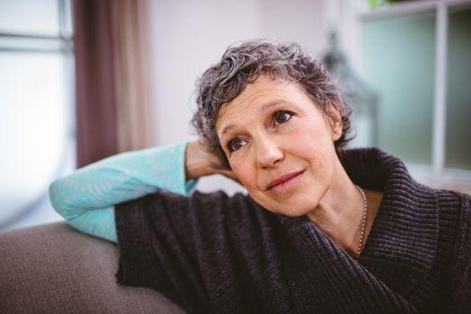 Thoughtful mature woman sitting on sofa