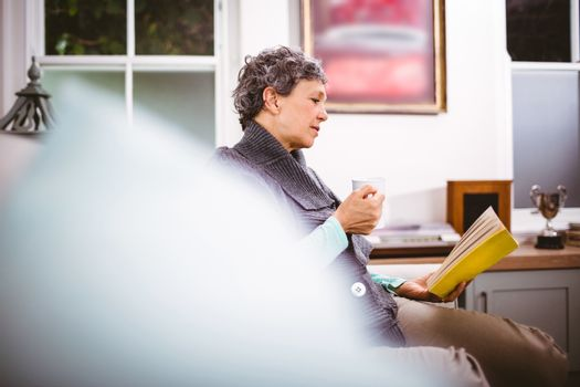 Mature woman reading book and holding coffee mug while sitting on sofa