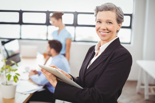 businesswoman using digital tablet with colleagues in background