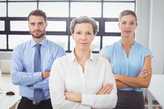 Portrait of confident business people by desk in office