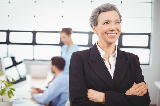 Confident businesswoman with colleague in background