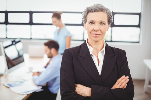 Confident businesswoman with colleague working in background