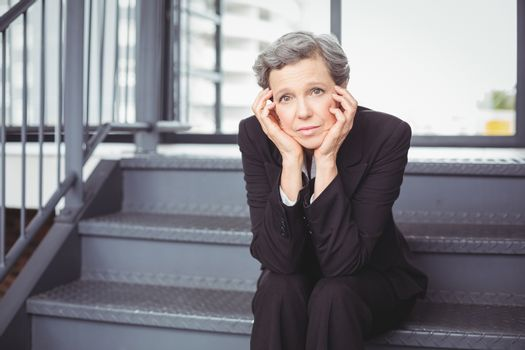 Thoughtful depressed businesswoman sitting on steps