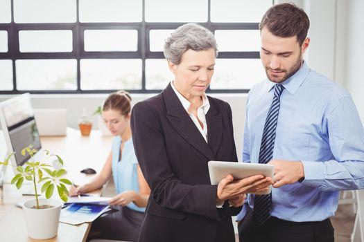 Businesswoman explaining male colleague over digital tablet