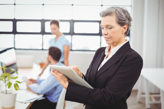 Businesswoman using digital tablet while colleagues in background