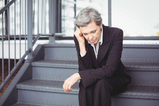 Upset businesswoman sitting on steps