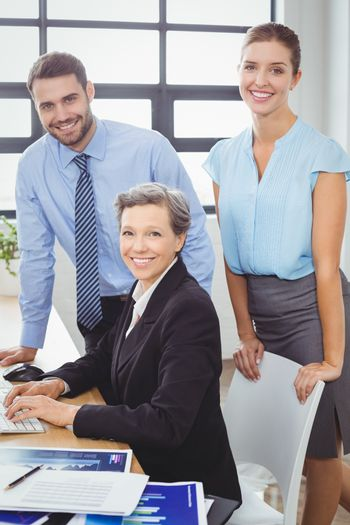 Confident business people at computer desk