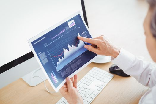 Businesswoman pointing on graph at computer desk