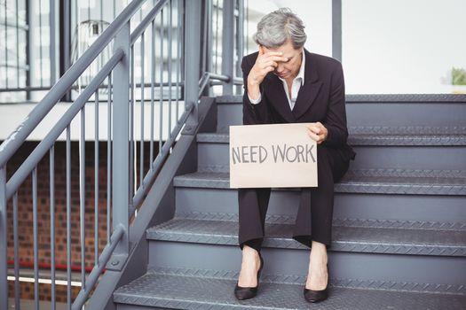 Unemployed businesswoman holding need work placard
