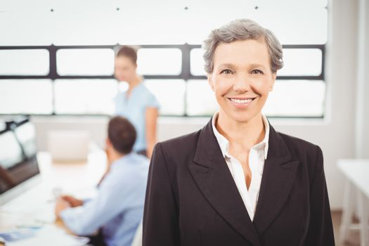 Happy businesswoman with colleagues working in background