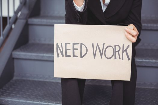Midsection of unemployed businesswoman with need work placard
