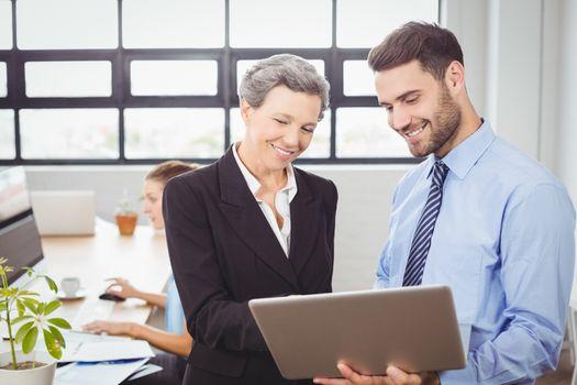 Business people looking in digital tablet at office