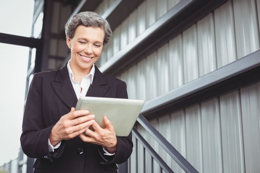 Businesswoman smiling while looking in digital tablet