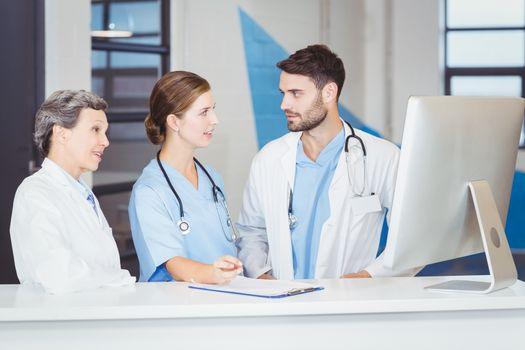 Doctors discussing at computer desk