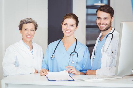 Portrait of smiling doctor team standing at computer desk
