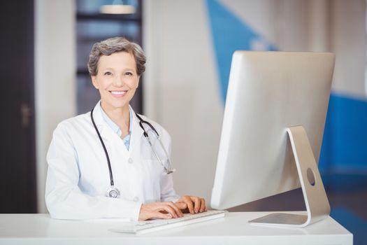 Portrait of smiling doctor working at computer desk