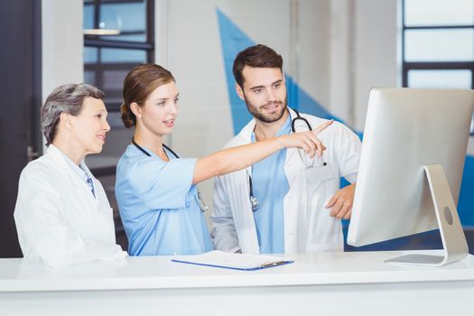 Doctor team discussing at computer desk
