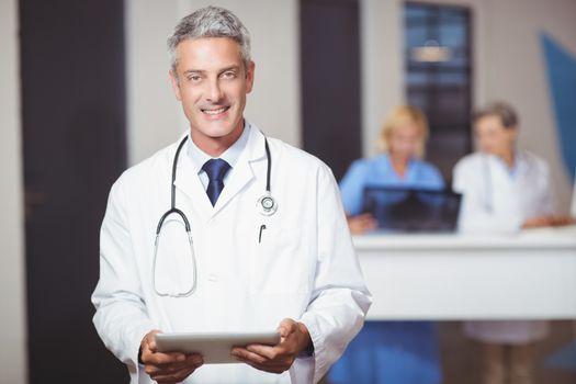 Portrait of smiling senior doctor holding digital tablet