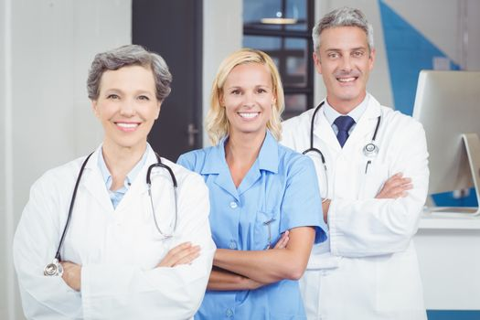 Portrait of smiling doctor team standing with arms crossed