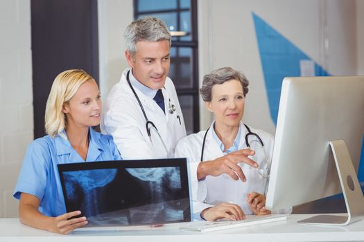 Doctor team with X-ray while discussing at computer desk