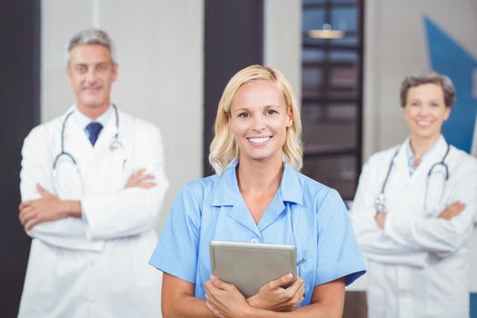 Portrait of cheerful doctor holding digital tablet while colleagues with arms crossed