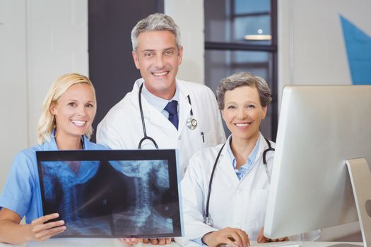 Portrait of smiling doctor team with X-ray