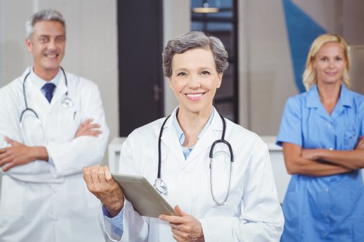 Cheerful doctor holding digital tablet while colleagues with arms crossed
