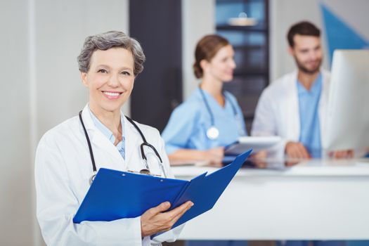 Portrait of happy female doctor holding medical reports