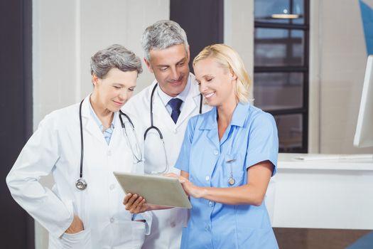 Smiling doctor team using digital tablet